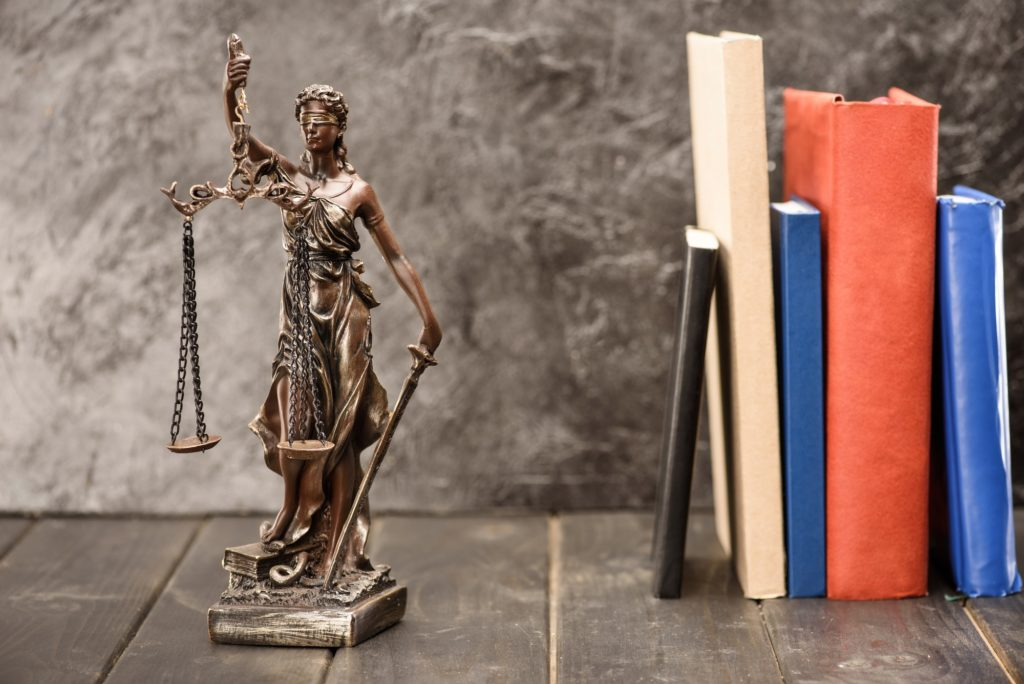 Close-up view of antique statue of lady justice and books, Law concept